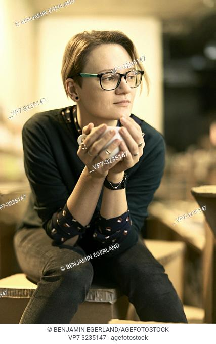 woman sitting indoors in café, holding coffee cup, in Munich, Germany