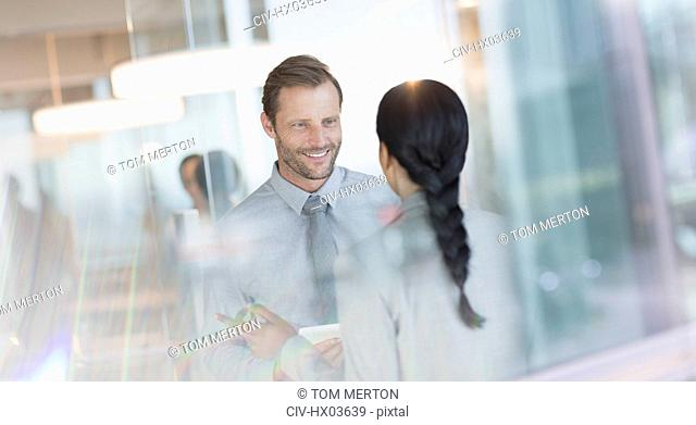 Smiling businessman talking to colleague in office