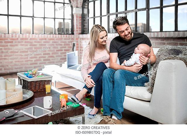 Mother and father sitting on sofa with baby girl