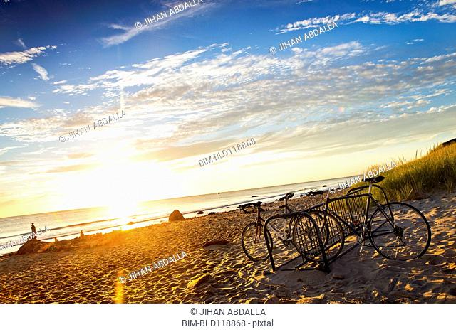 Bicycles parked on beach at sunset