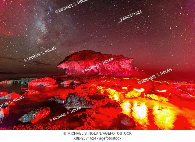Night view of the shoreline with red light on rocks at Himalaya Beach, Sonora, Mexico