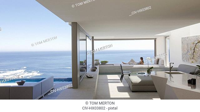 Woman relaxing on modern, luxury home showcase patio with sunny ocean view