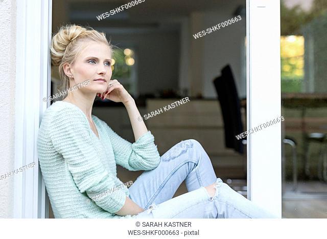 Blond woman sitting at terrace door