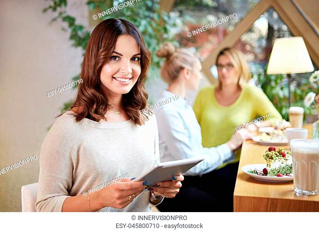 Portrait of beautiful woman at cafe eating cake and using tablet