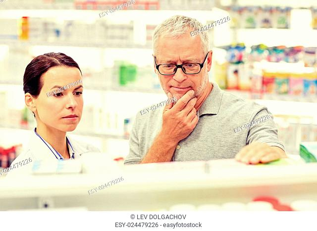 medicine, pharmaceutics, health care and people concept - pharmacist showing drug to senior man customer at drugstore