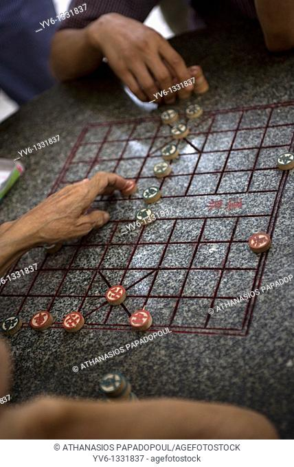 CHINA HONG KONG KOWLOON YAU MA TEI SHANGHAI AND MARKET STREET Image of cropped arms playing Chinese chess on a marbled chess table at an open space outside Tin...