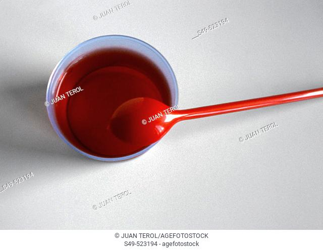 Strawberry jelly and red plastic spoon