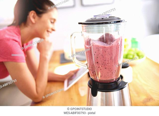 Young woman using tablet in the kitchen while preparing smoothie