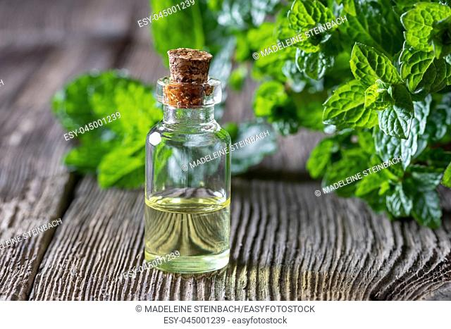 A bottle of essential oil with fresh peppermint leaves on a wooden background