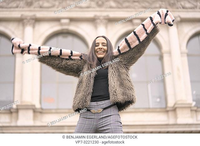 playful woman in fashionable winter clothes, playing with scarf, pure happiness, candid emotion, in front of wealthy historical architecture, in Munich, Germany