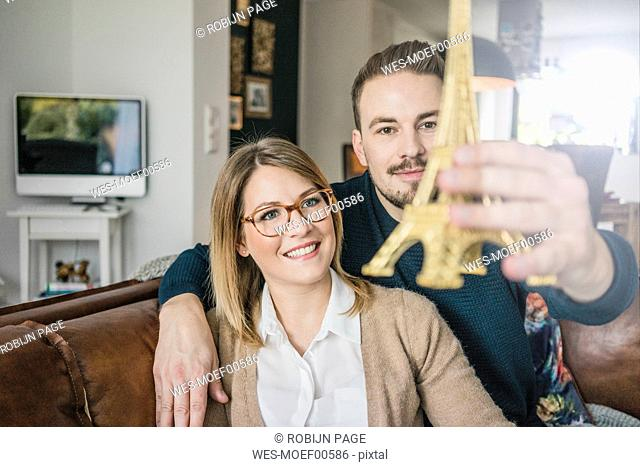 Smiling couple sitting on couch at home holding Eiffel tower model