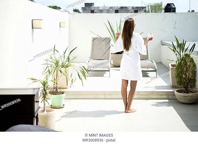 Rear view of a woman wearing a bathrobe standing in front of loungers
