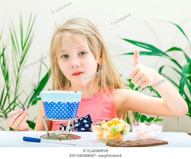 Little girl preparing and eating a chocolate fondue. Chocolate fondue with kiwi, banana, apple, tangerine and marshmallow. Happy little girl