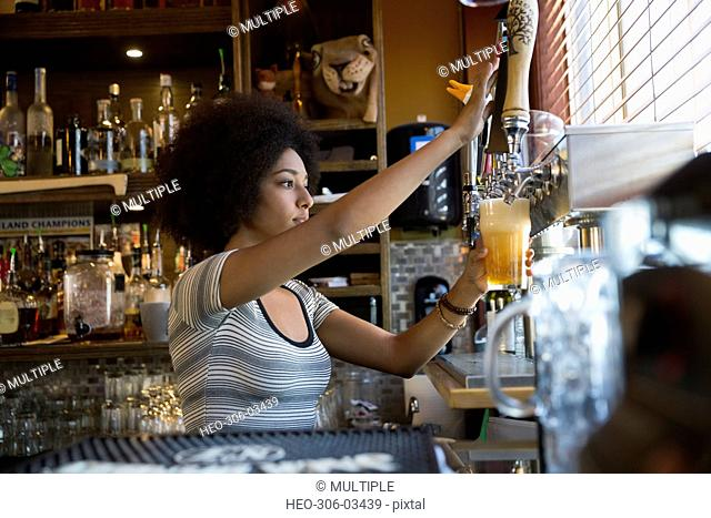 Bartender pouring beer from tap behind counter