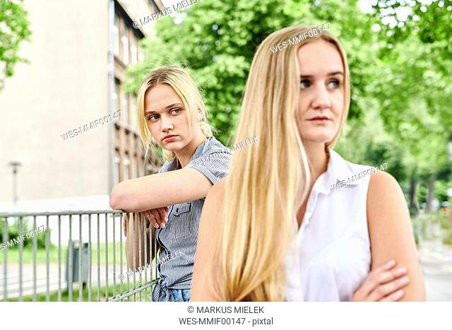 Two discontented young women outdoors