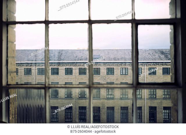 Salts Mill building seen trough a window. Saltaire Village, Shipley, Bradford, West Yorkshire, England, UK, Europe