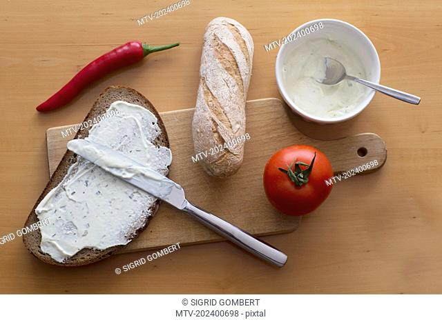 Cheese spreading on slice of brown bread with baguette and tomato on chopping board