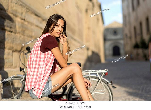 Spain, Baeza, portrait of young woman with bicycle resting at sunlight