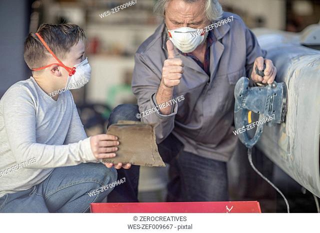 Senior man and boy sanding car