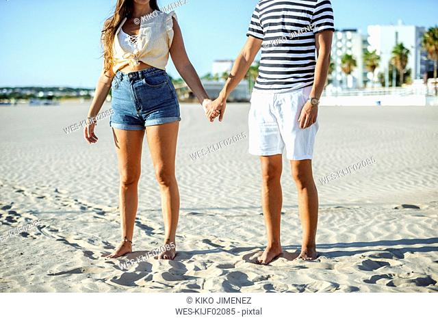 Close-up of couple holding hands on the beach