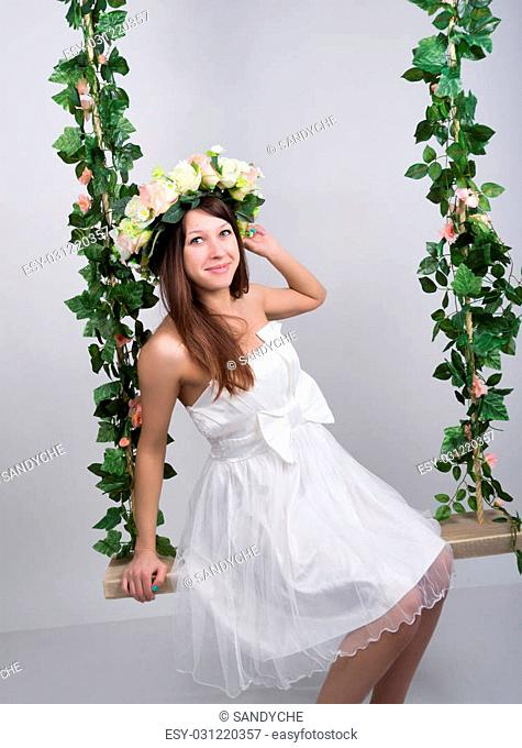 Beautiful young leggy blonde in a little white dress on a swing, wooden swing suspended from a rope hemp, rope wrapped vine and ivy