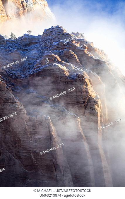 Fog and snow penetrate the sheer canyon walls of Zion National Park, Utah