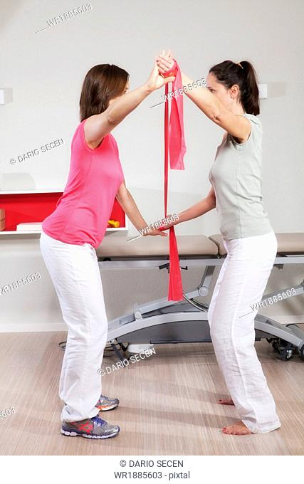 Female osteopath training with patient, using a resistance band, Munich, Bavaria, Germany