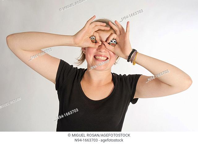 Blonde girl holding her hands in the shape of a pair of binoculars in front of her eyes