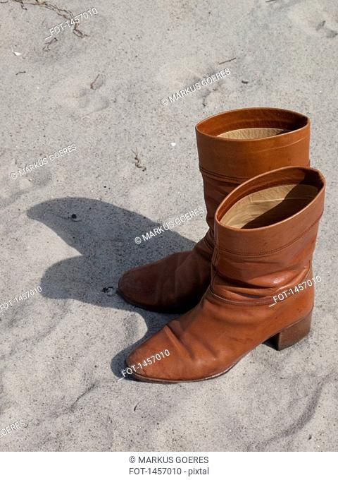High angle view of leather boots on sand