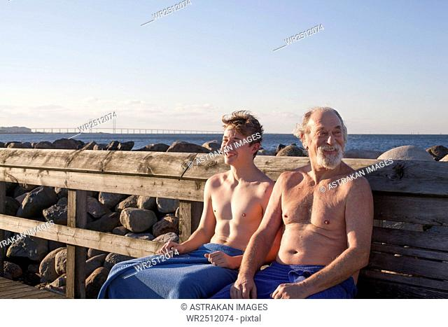 Father and son sitting on bench against clear blue sky