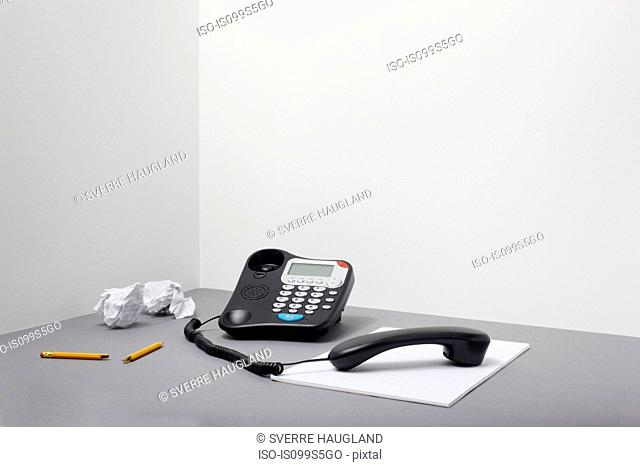 Landline office phone off the hook with pencil and paper