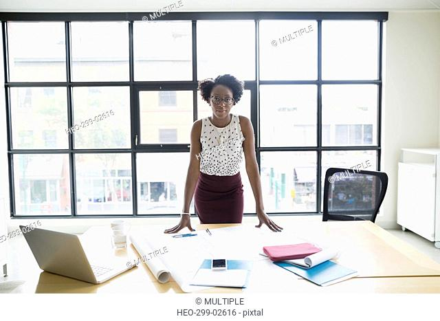 Portrait confident female architect standing at conference room table with blueprints