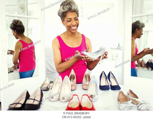 Smiling mature woman looking at high heels in closet