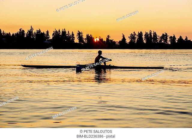 Silhouette of Caucasian man rowing at sunset