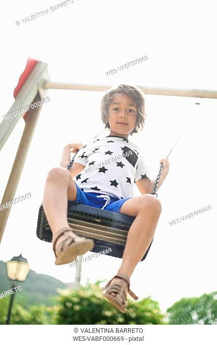 Portrait of little boy on a swing