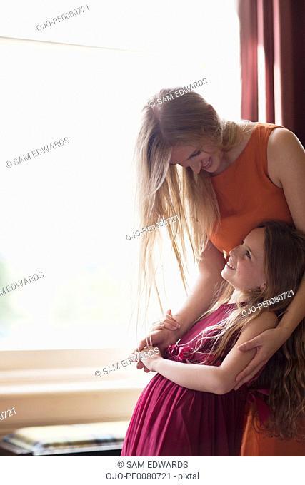 Sisters hugging near window