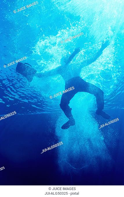 Underview, businessman jumping into pool