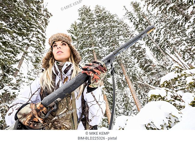 Caucasian woman hunting in forest holding rifle