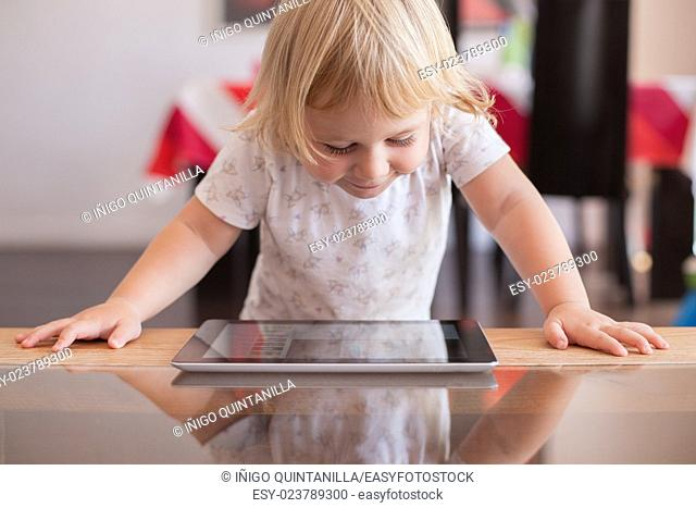 blonde two years old baby white shirt smiling happy face reading and watching digital tablet on wood and crystal table indoor at home
