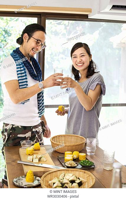 Smiling man and woman standing indoors by a table set with food, holding drinking glasses, toasting