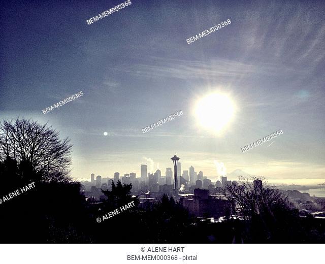 Sun rising over city skyline, Seattle, Washington, United States
