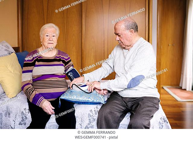Senior man checking blood pressure of his wife at home