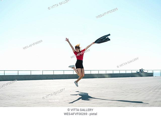 Fashionable young woman jumping on waterfront promenade