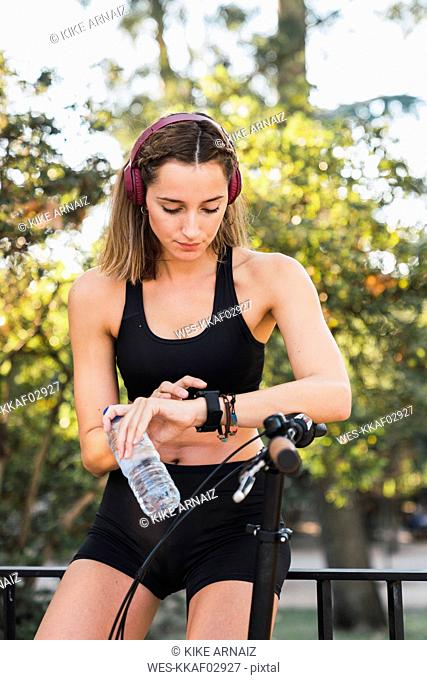 Fit young woman taking a break, holding bottle of water