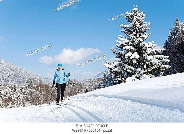 Germany, Bavaria, Aschermoos, Senior woman doing cross-country skiing