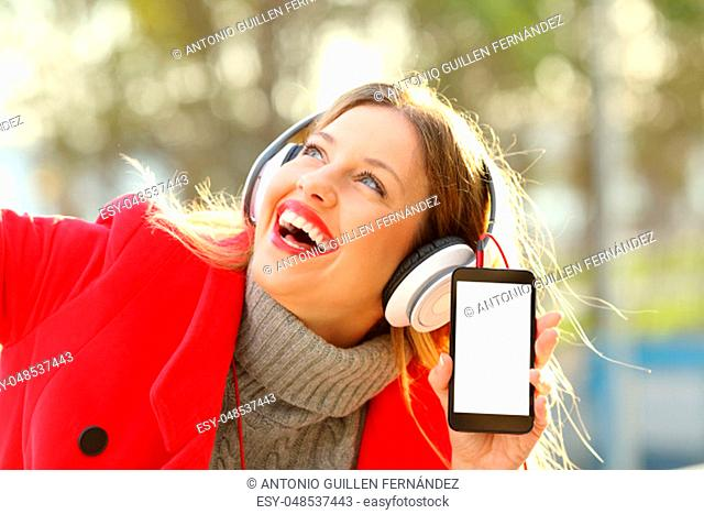 Happy girl wearing red jacket and headphones listening to music and showing smartphone screen in a park in winter