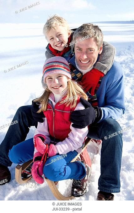 Portrait of smiling father with daughter and son on sled in snow