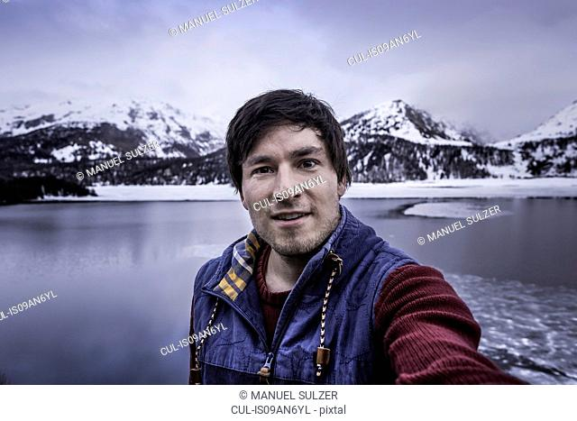 Male hiker taking selfie at lake Silsersee, Malojapass, Graubunden, Switzerland