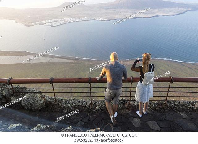 Young couple watching the abyss. Mirador del Rio, Lanzarote. Spain