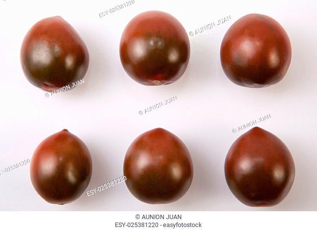 Dark green cherry tomatoes. Isolated over white background